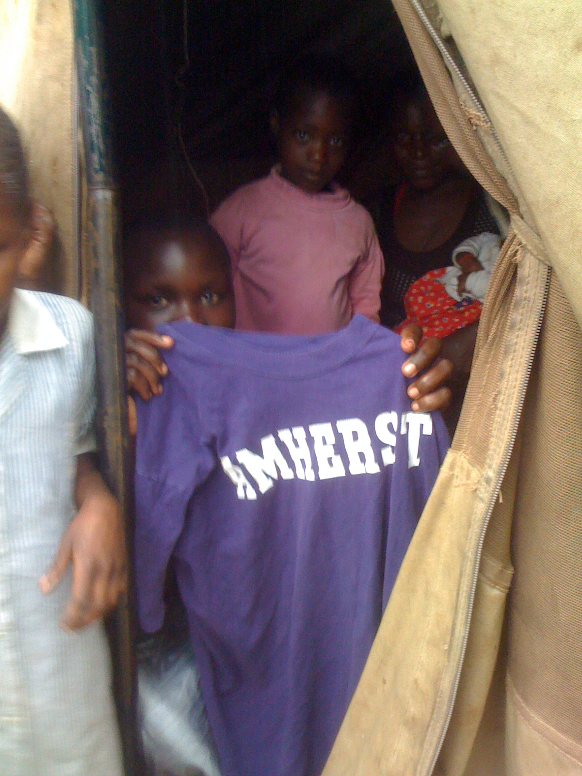 Ugandan Child holding an Amherst t-shirt