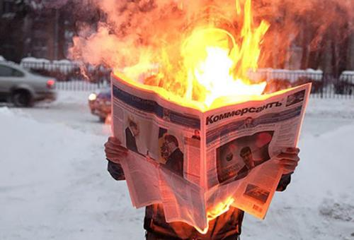 Conceptual photo of solitary figure reading a burning newspaper against a snowy landscape, exploring how human consciousness reacts to the flow of information by being constantly bombarded with 'hot news' until it reaches a critical point.