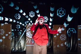 Actor in a red jacket performs in the play, Peer Gynt