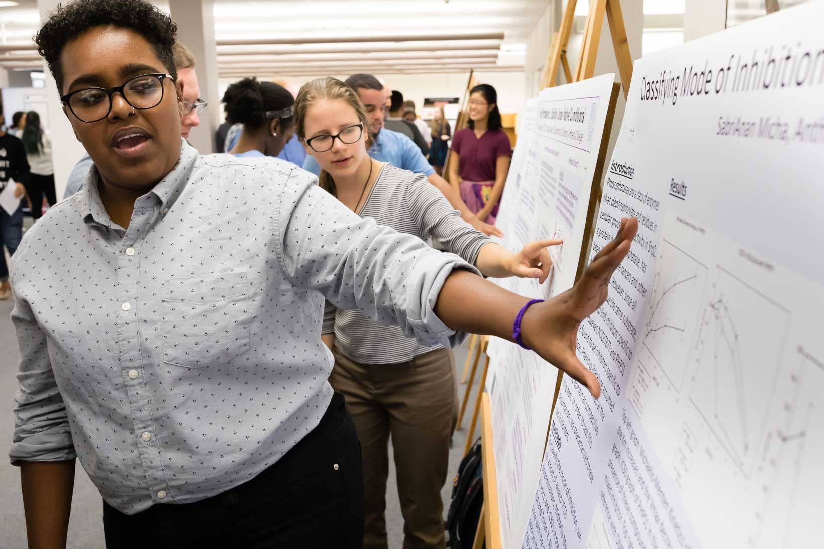 SabriAnan Micha '19 explains their science project to fellow students and professors.