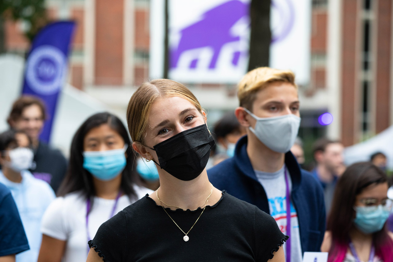 a student tilts her head and smiles under her mask