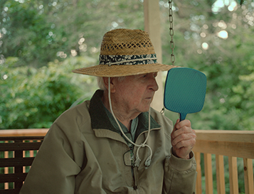 An old man wearing a hat looking into a handheld mirror