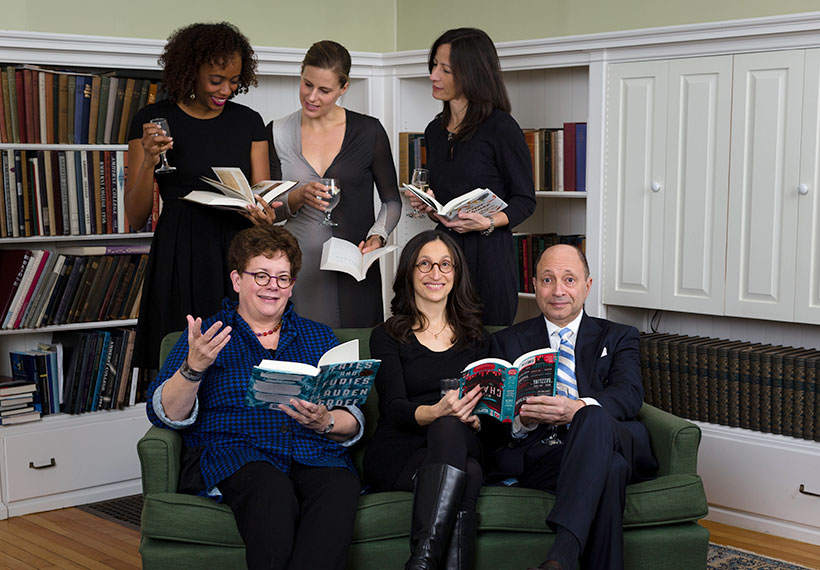 Six people posing together 3 sitting on a couch, 3 standing, all holding books and smiling