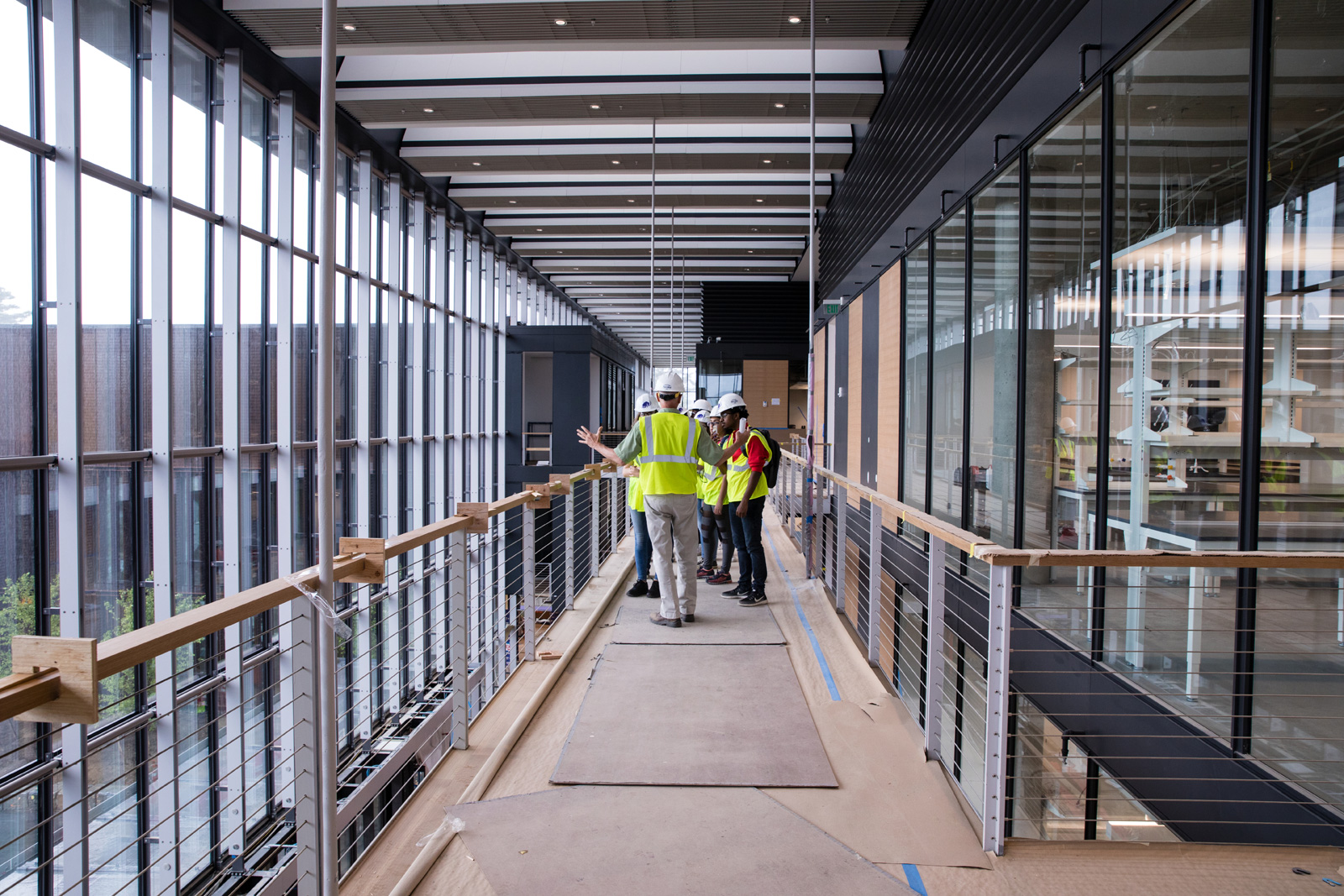 People in hard hats standing on a corridor in front of the front glass wall of the Science Center.