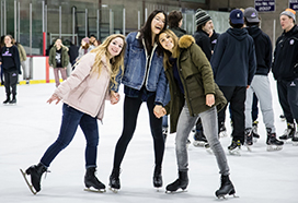 Three students posing on ice skates