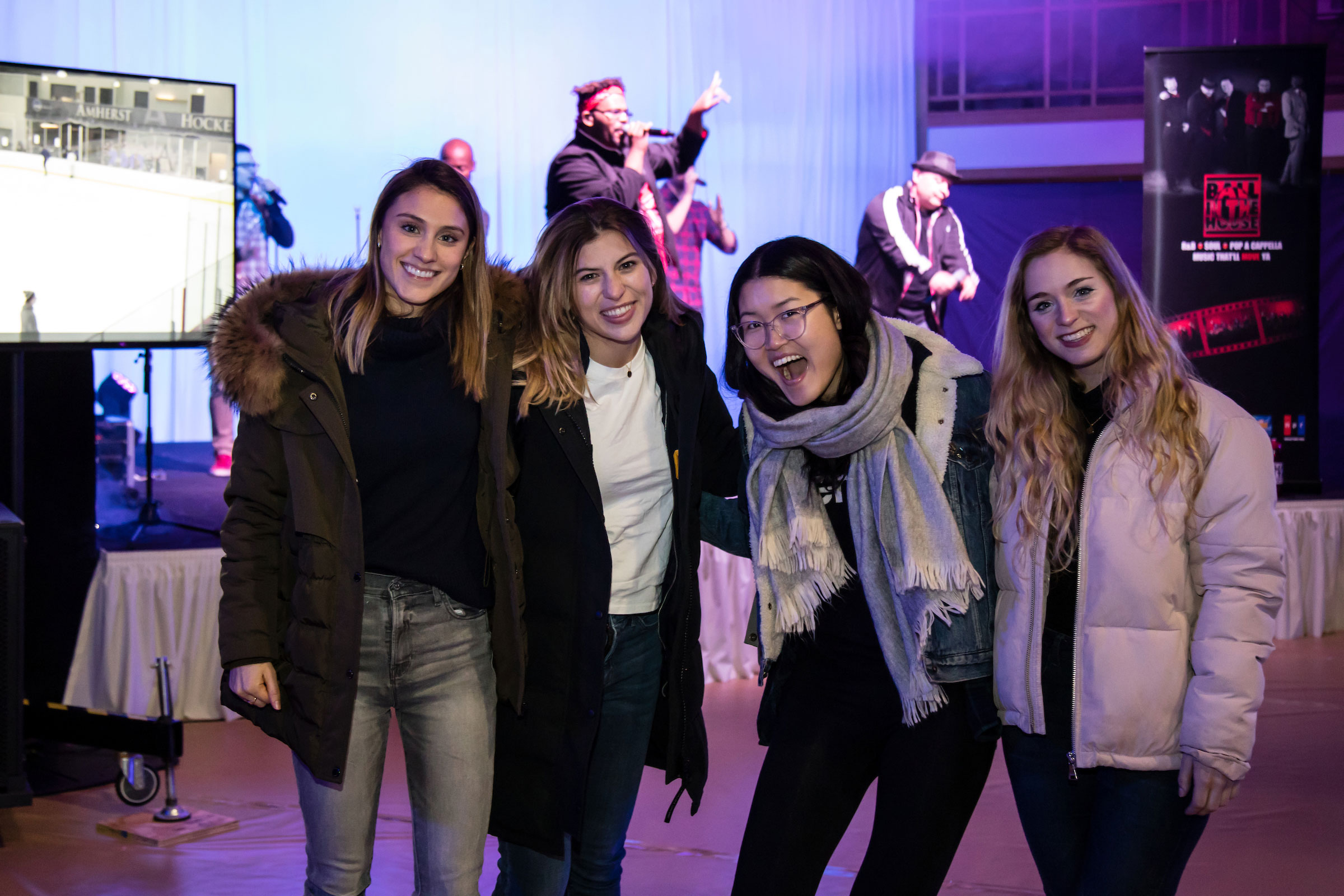Four smiling women pose in front of the band at Winter Fest