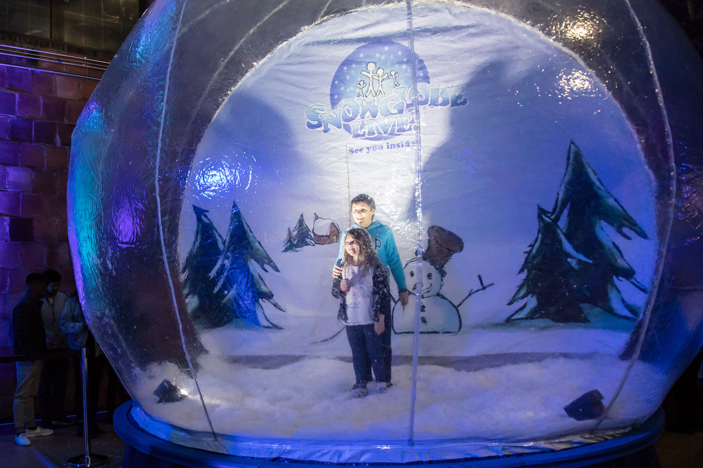 Two children pose inside an inflatable snow globe