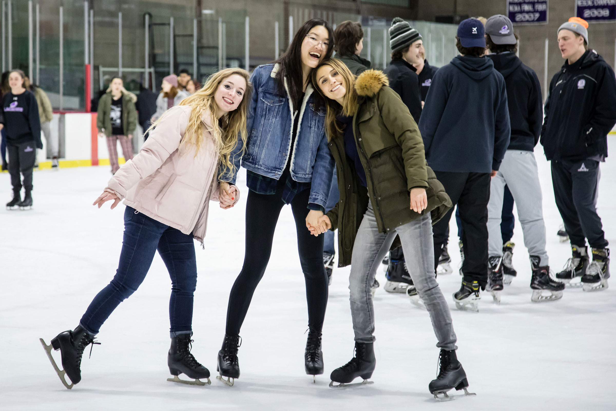 Three women pose together on the ice skating rink