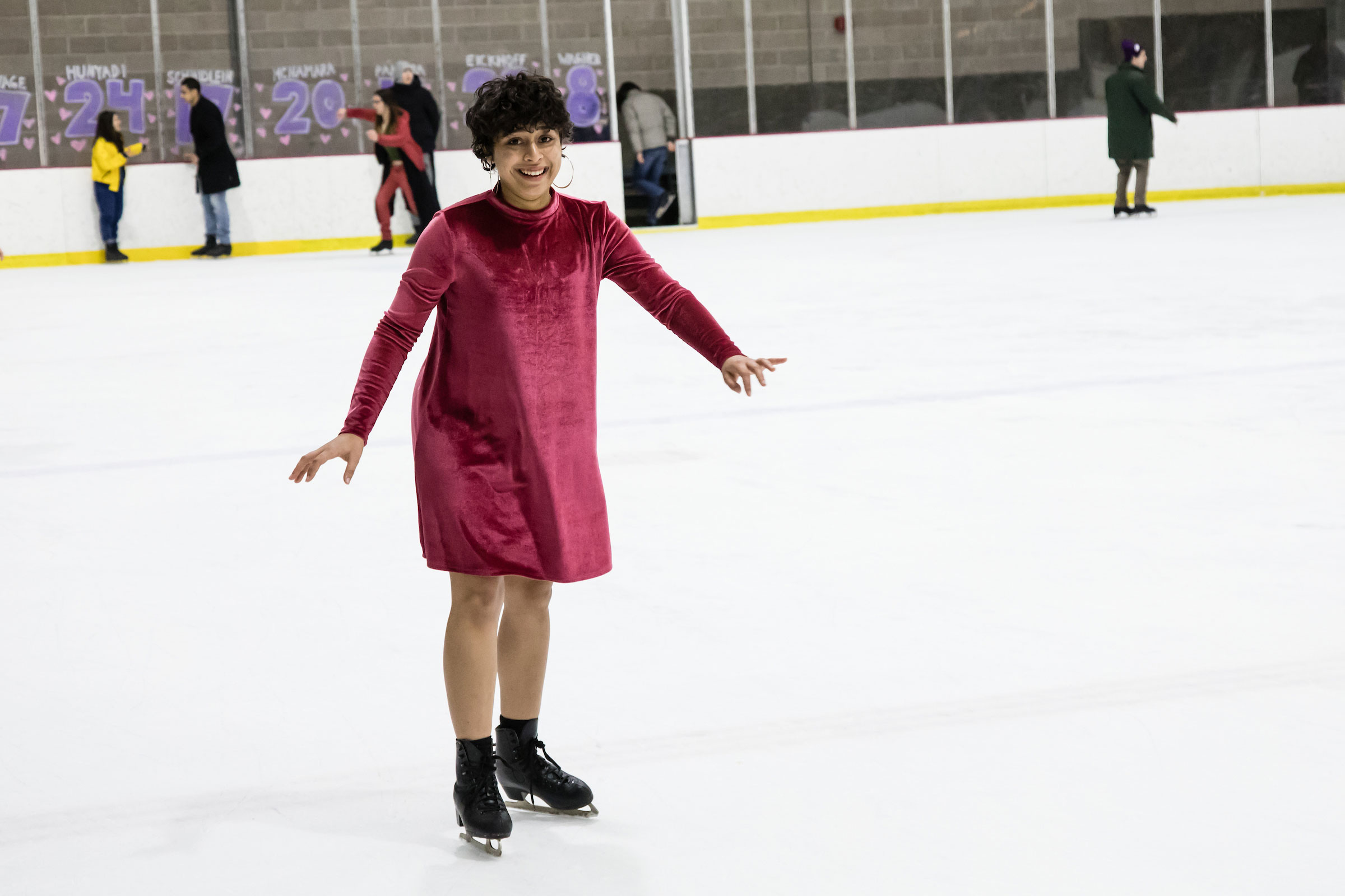 A young girl in a red dress ice skating