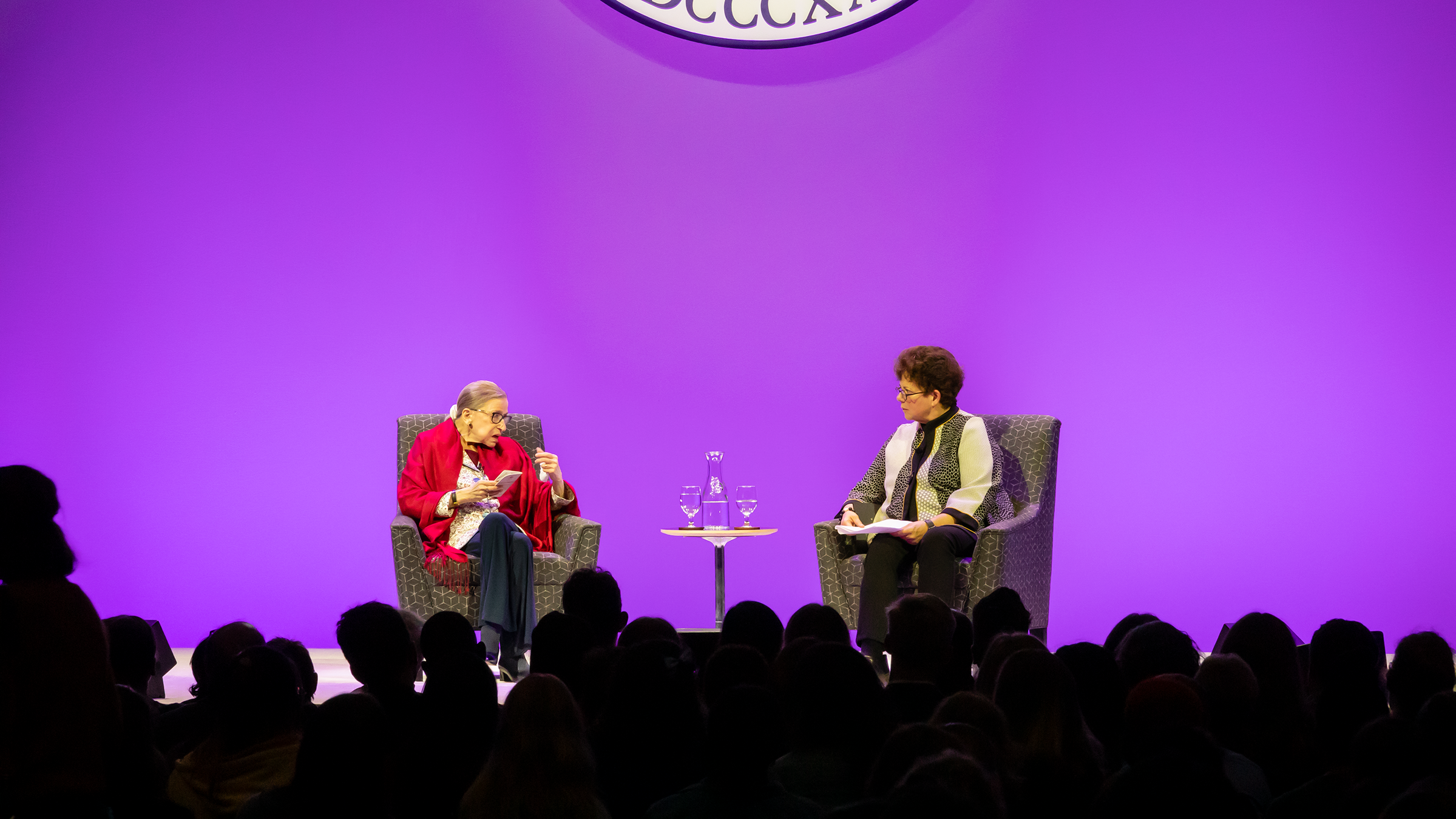A photo of Ruth Bader Ginsburg speaking with President Biddy Martin on stage against a purple background