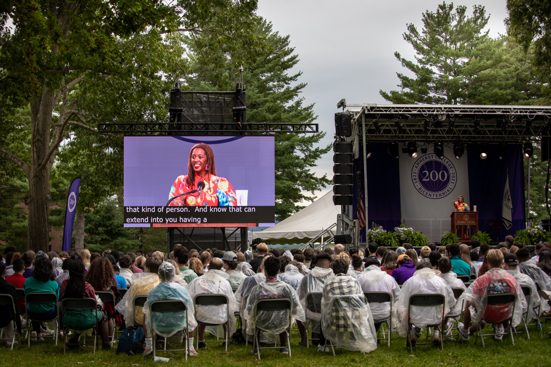 Professor Shayla Lawson on a screen speaking on the Amherst College quad