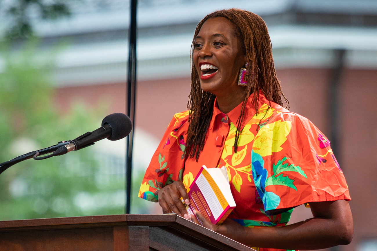 A woman in a bright orange shirt smiling at a podium