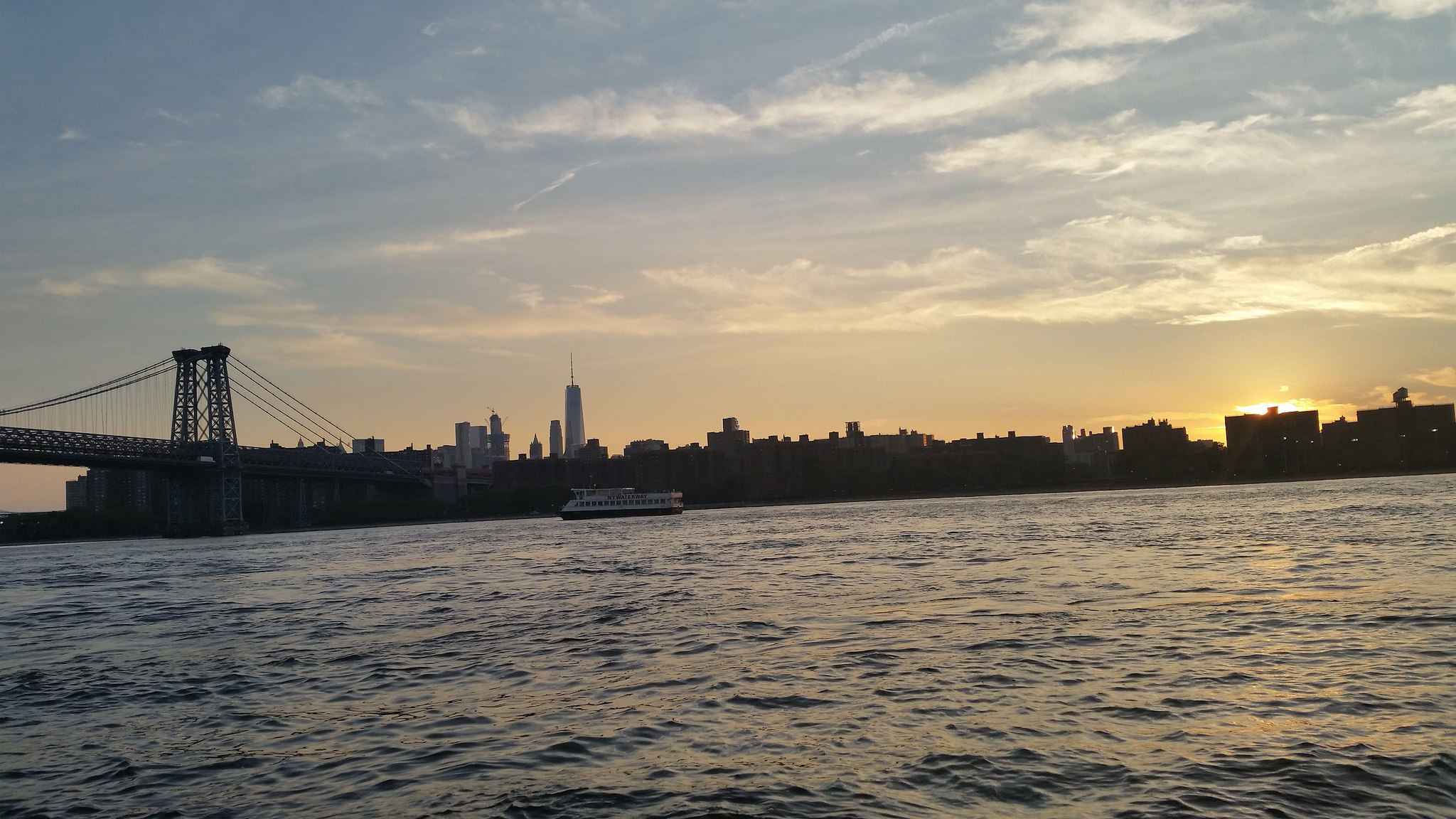 A photo from Grand Ferry Park looking over the water towards New York City at sunset.