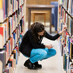 A young woman looking through a shelf of books