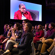 A group of students with a large video screen showing Ruth Bader Ginsberg