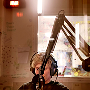 A young man in a radio studio speaking into a microphone