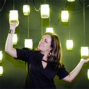 A woman reaching up and holding bright lights