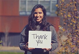 "Student holding a ""thank you"" sign"
