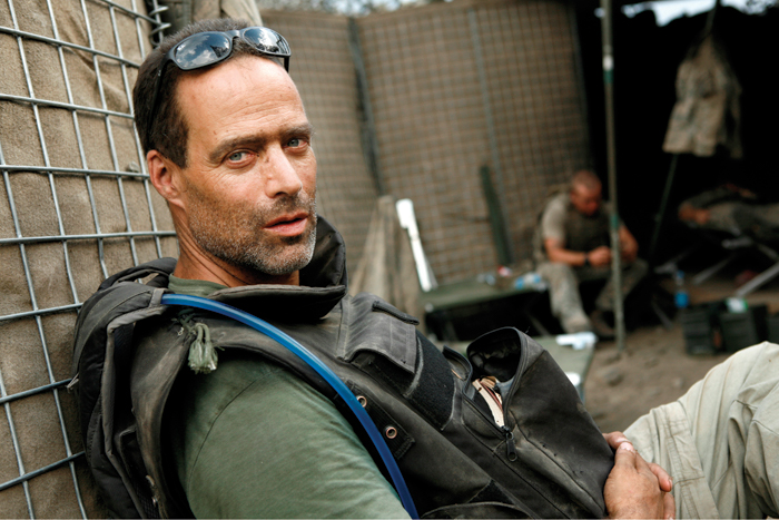 Sebastian Junger sitting leaning against a fence, looking at the camera