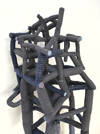 A piece of abstract art sculpture made up of gray twisting tubes