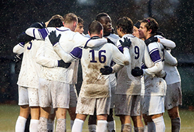 Men's soccer team in a huddle