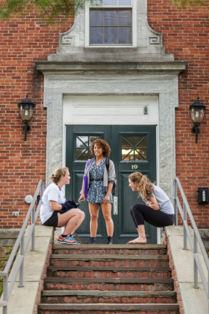 Three students talking on the steps of a dorm