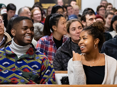 Two students laughing and sitting together in Johnson Chapel