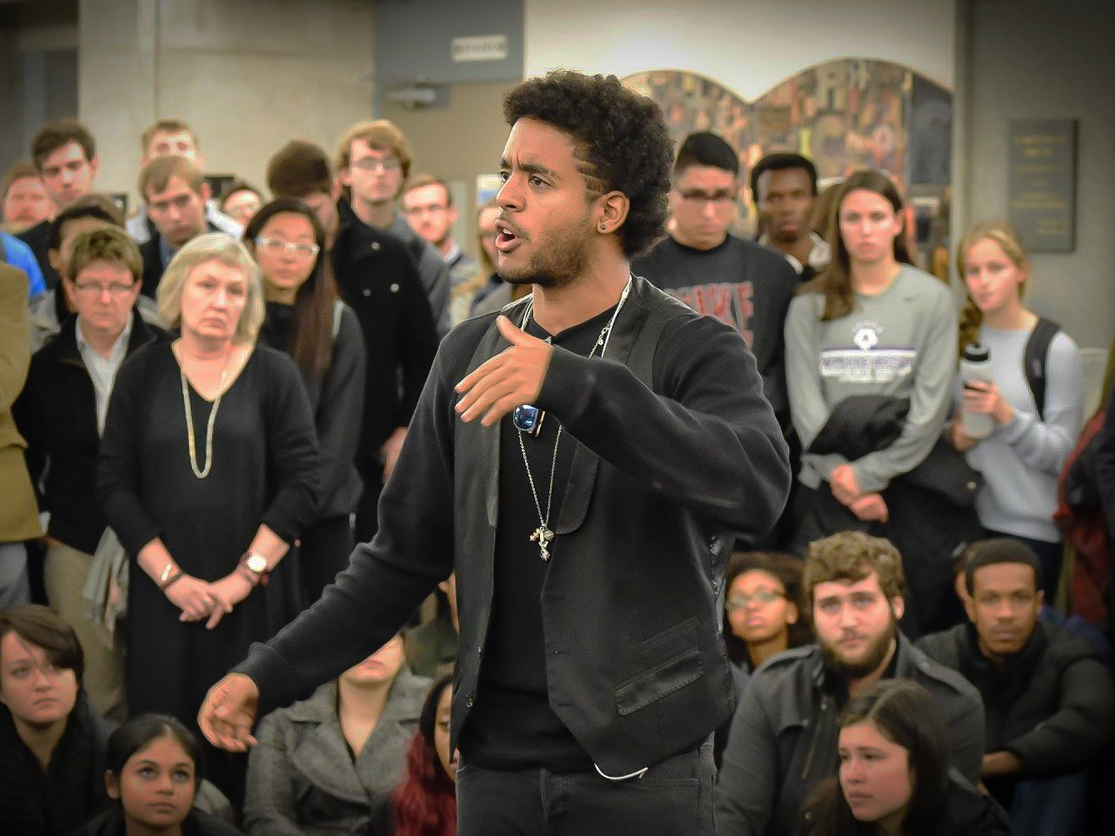 A young Black man speaking in front of a group of people