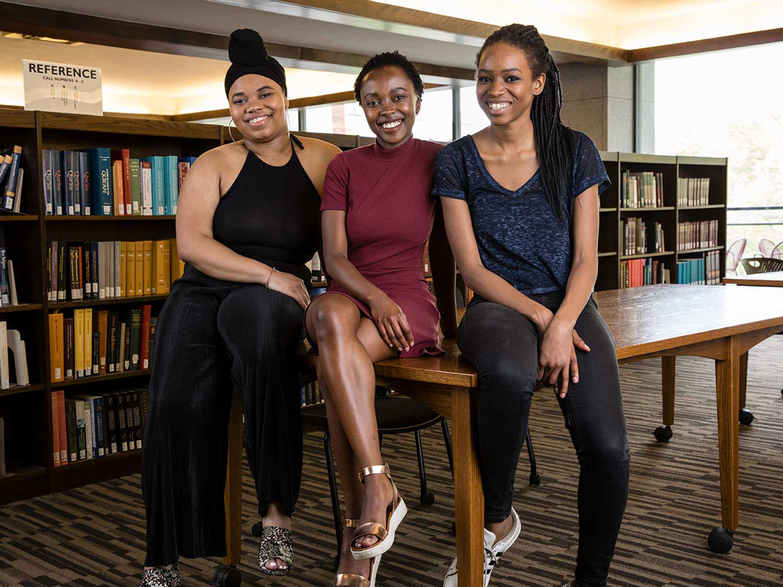 Three Black woman sitting on a table in a library smiling