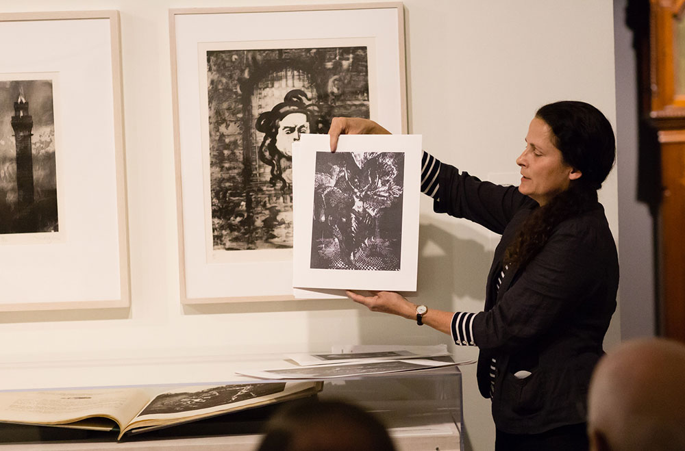 "Senior Resident Artist Betsey Garand holds a copy of ""The Dance of Salomé,"" a woodcut included in Mazur's senior thesis project ""An Image of Salomé,"" which is displayed in the case."