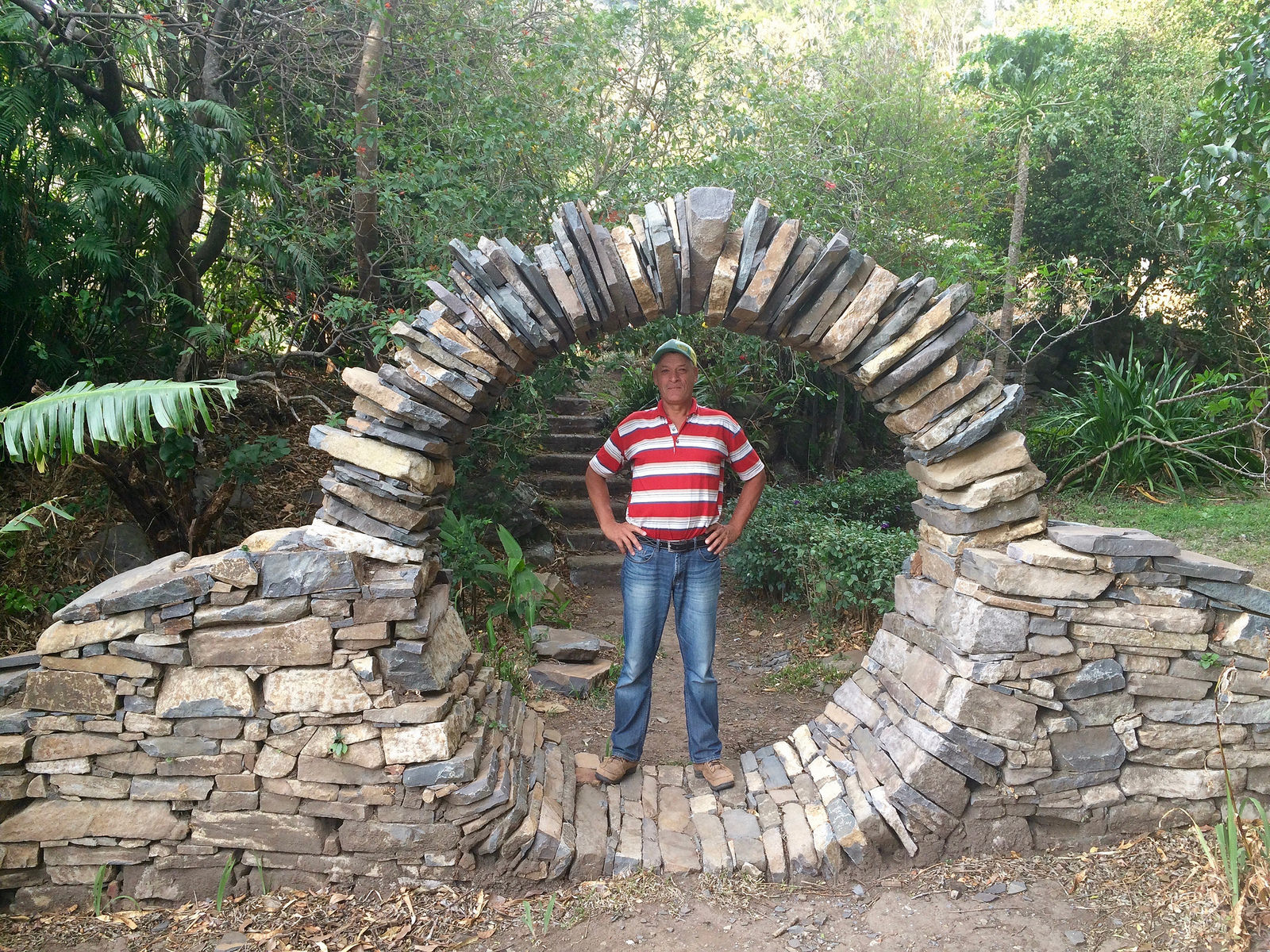 man standing in a circular arch of stones