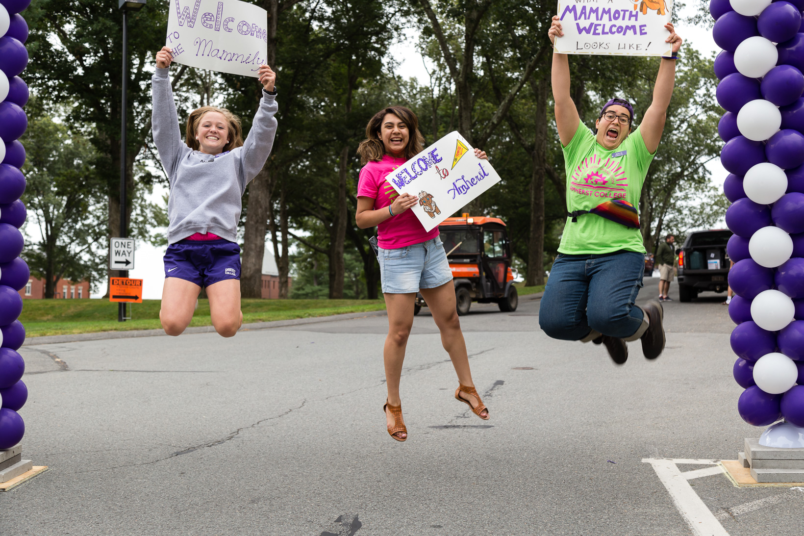 Students, holding signs and jumping in the air welcome the incoming class during Orientation.
