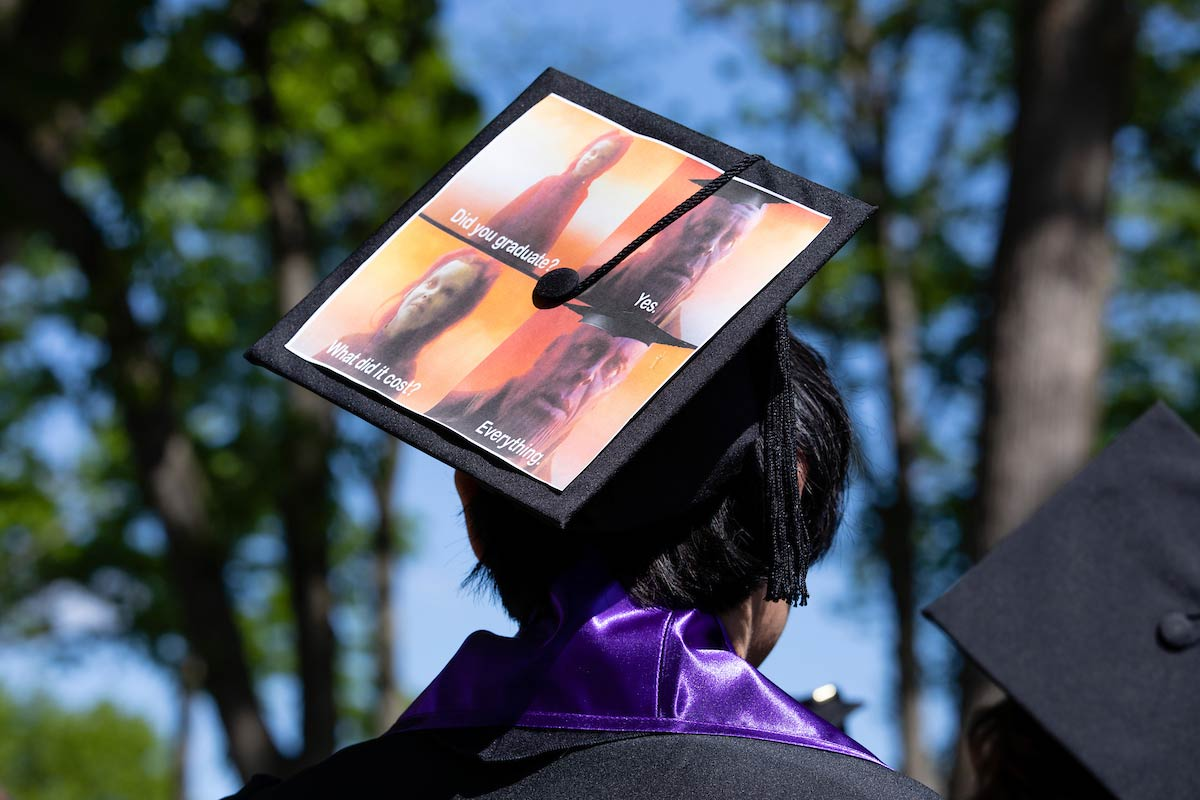 A student with a decorated mortar board at Amherst College's 198th Commencement