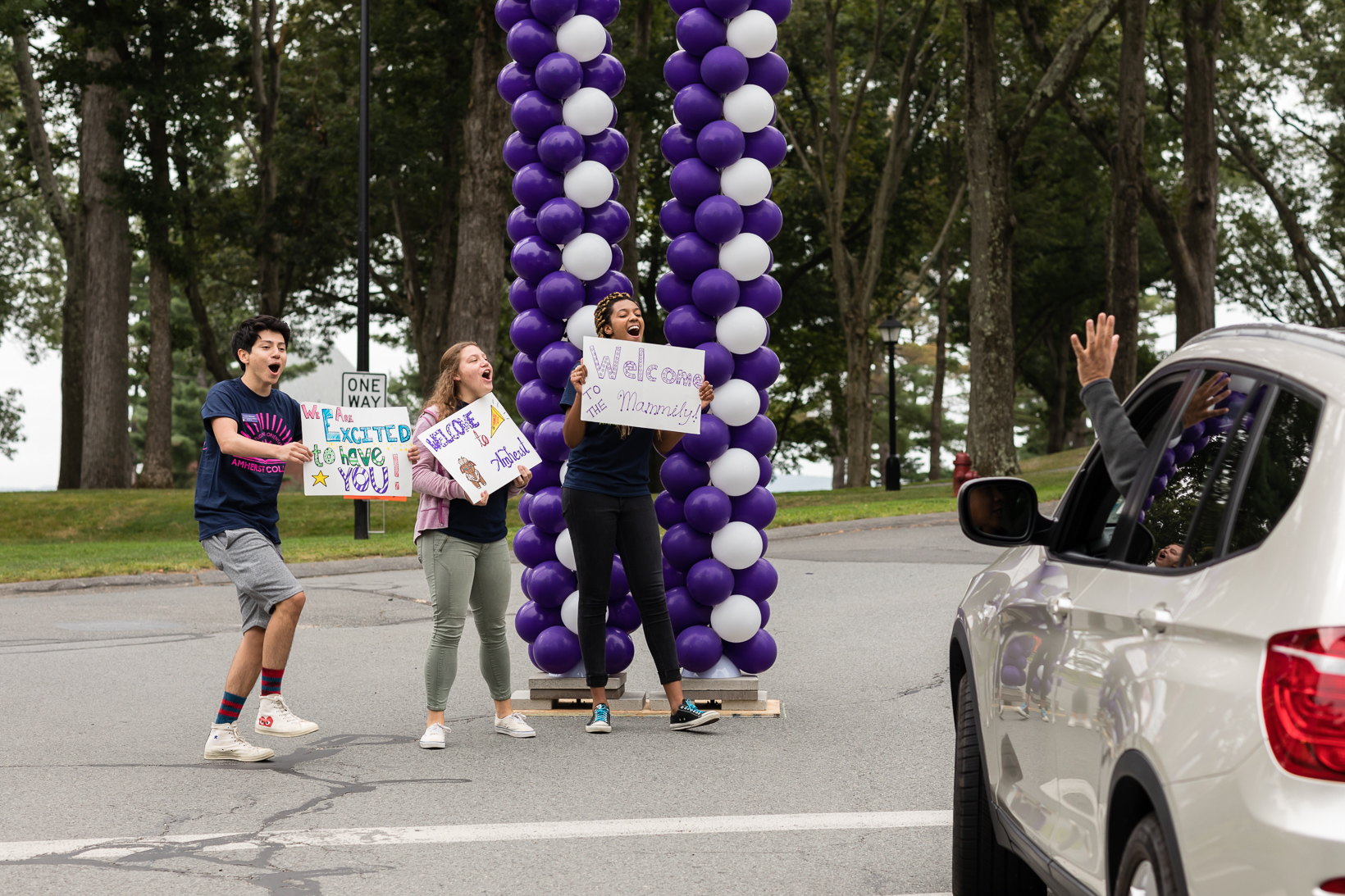Students, standing beside an archway made of purple and white ballons, greet the new students and there families.
