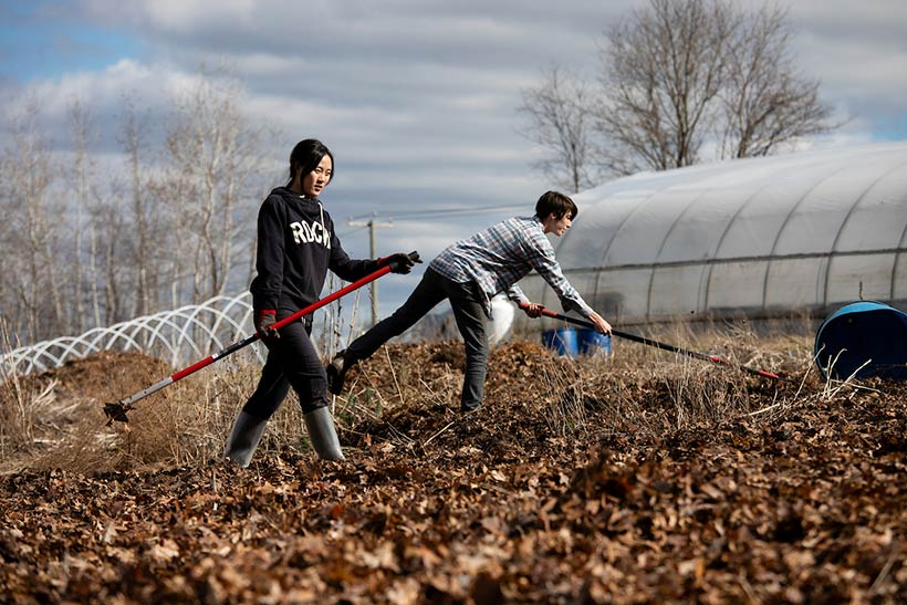 A student and a farm staff member raking in a garden