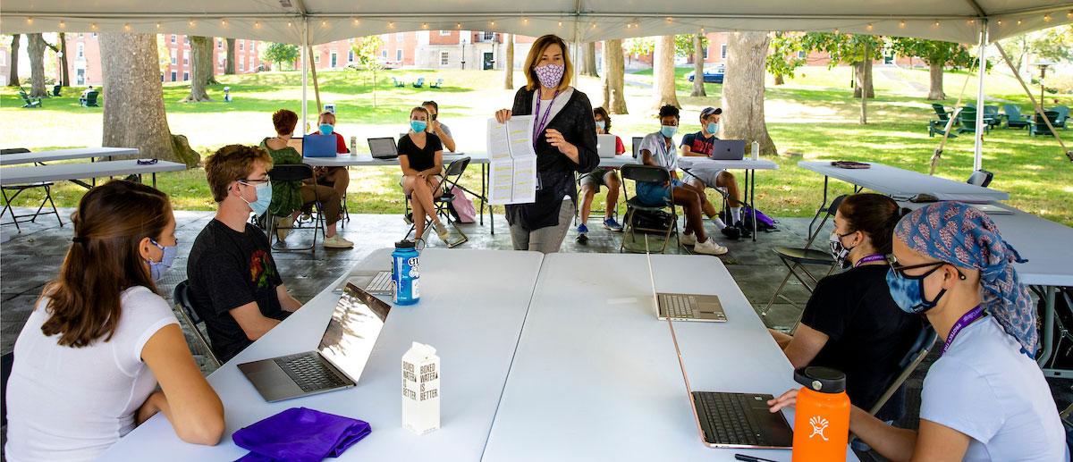 A professor teaching a class outside under a tent