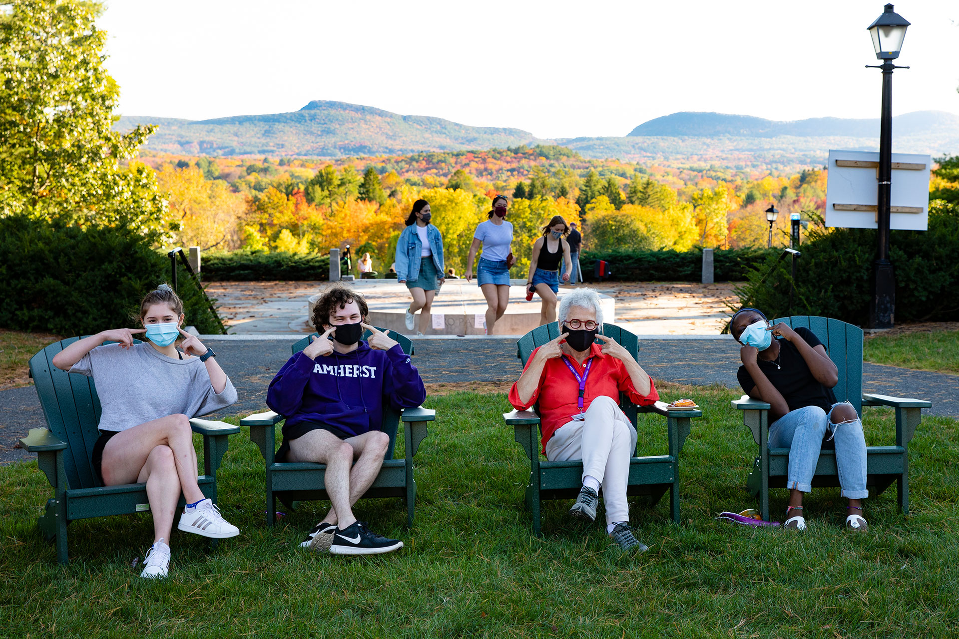 Four people wearing masks sitting on the quad in front of memorial hill