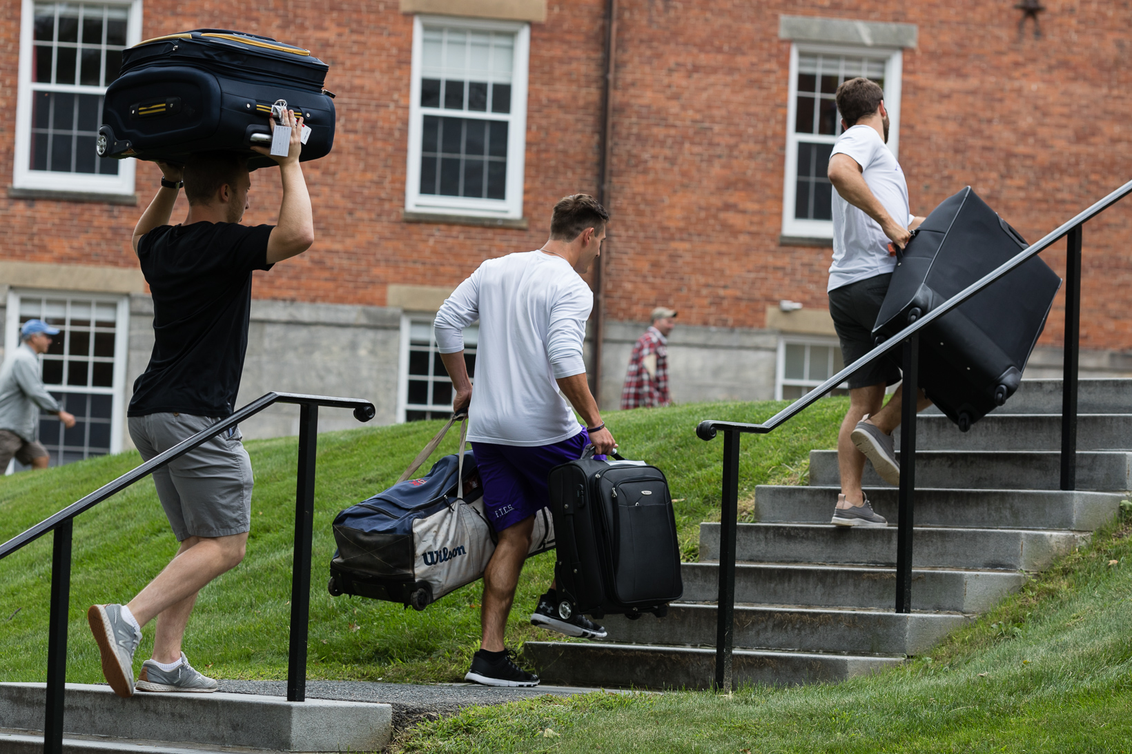 Students carrying large suitcases up a set of stairs.