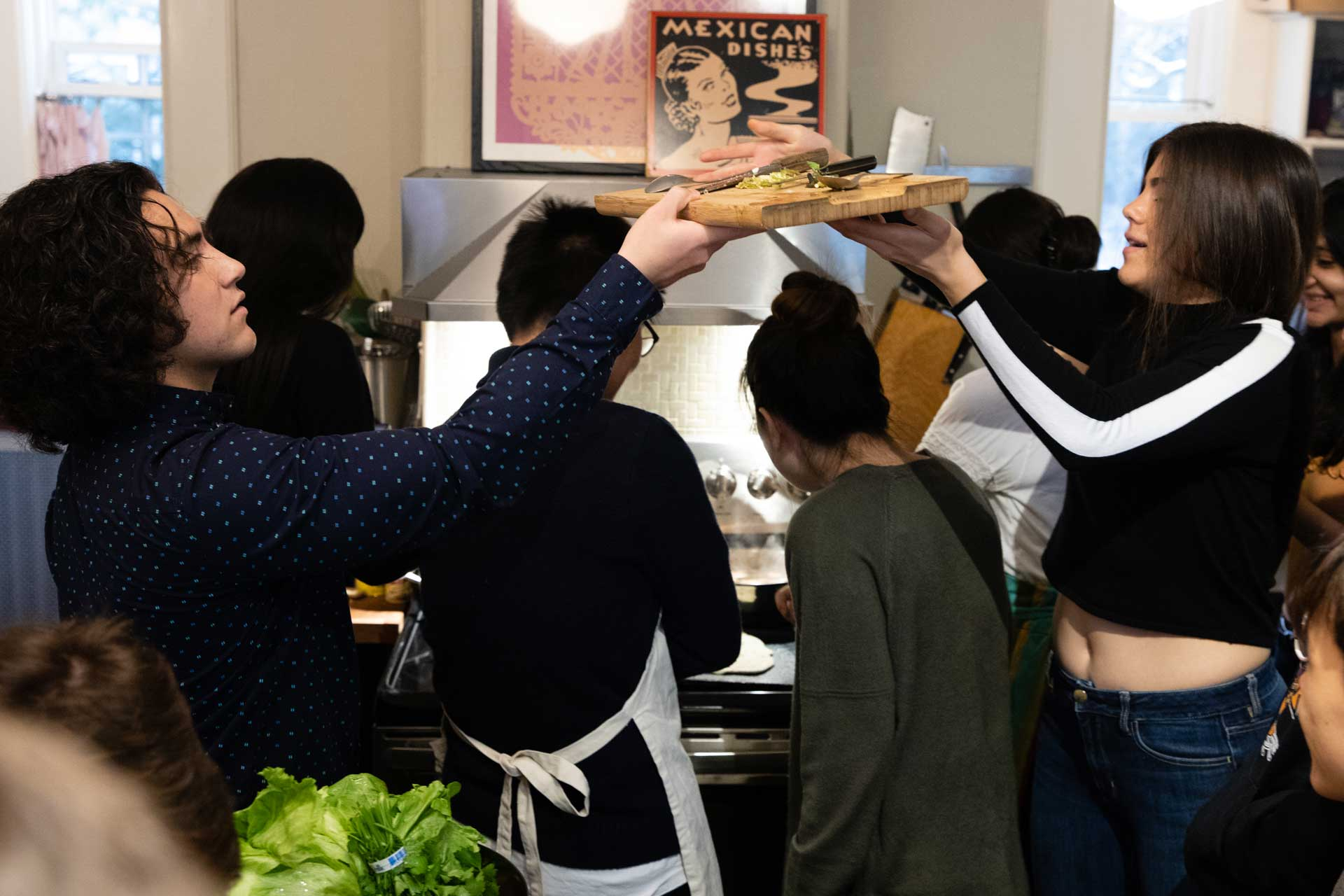 A group of student preparing food together in a kitchen