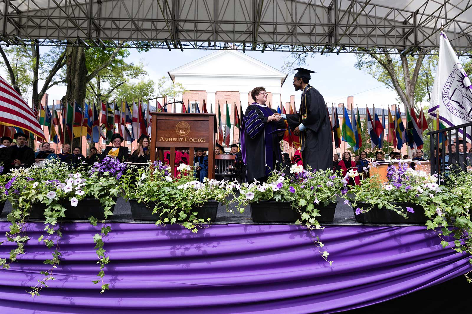 President Biddy Martin shaking hands with a graduate