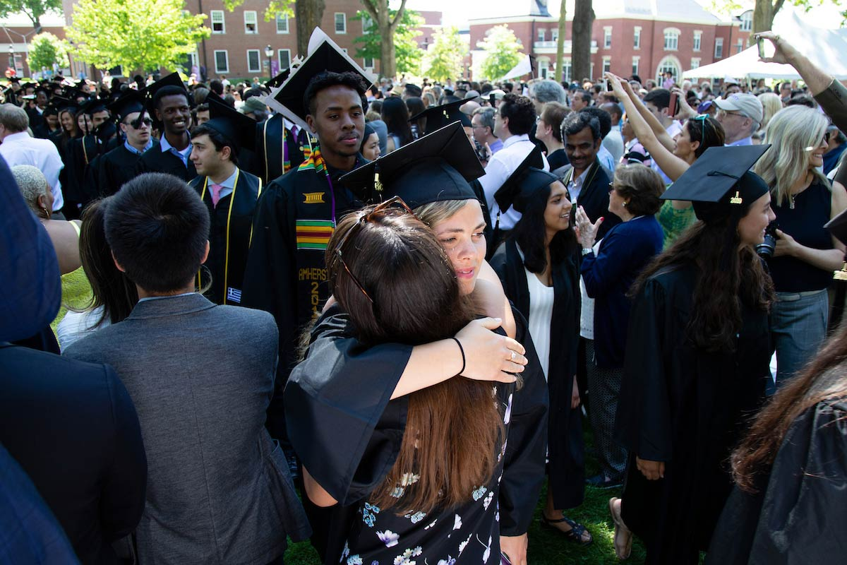 An Amherst College graduate hugs a well-wisher