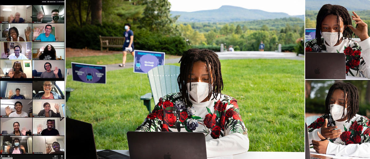 a student sitting on the main quad participates in a zoom class with a view of the holyoke range in the background