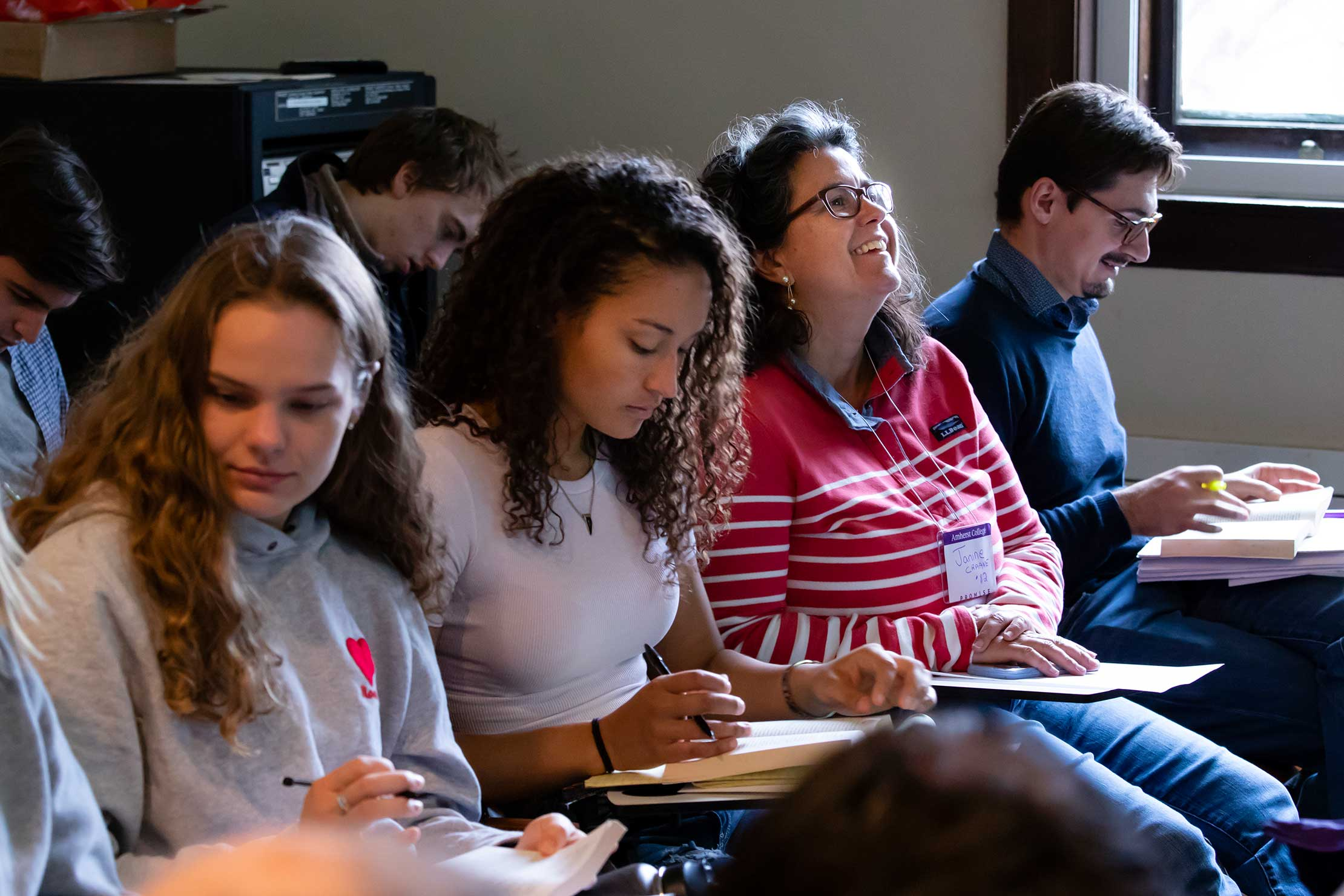 A Homecoming attendee sits among the students in Professor Katsaros' class, taught in Fayerweather.