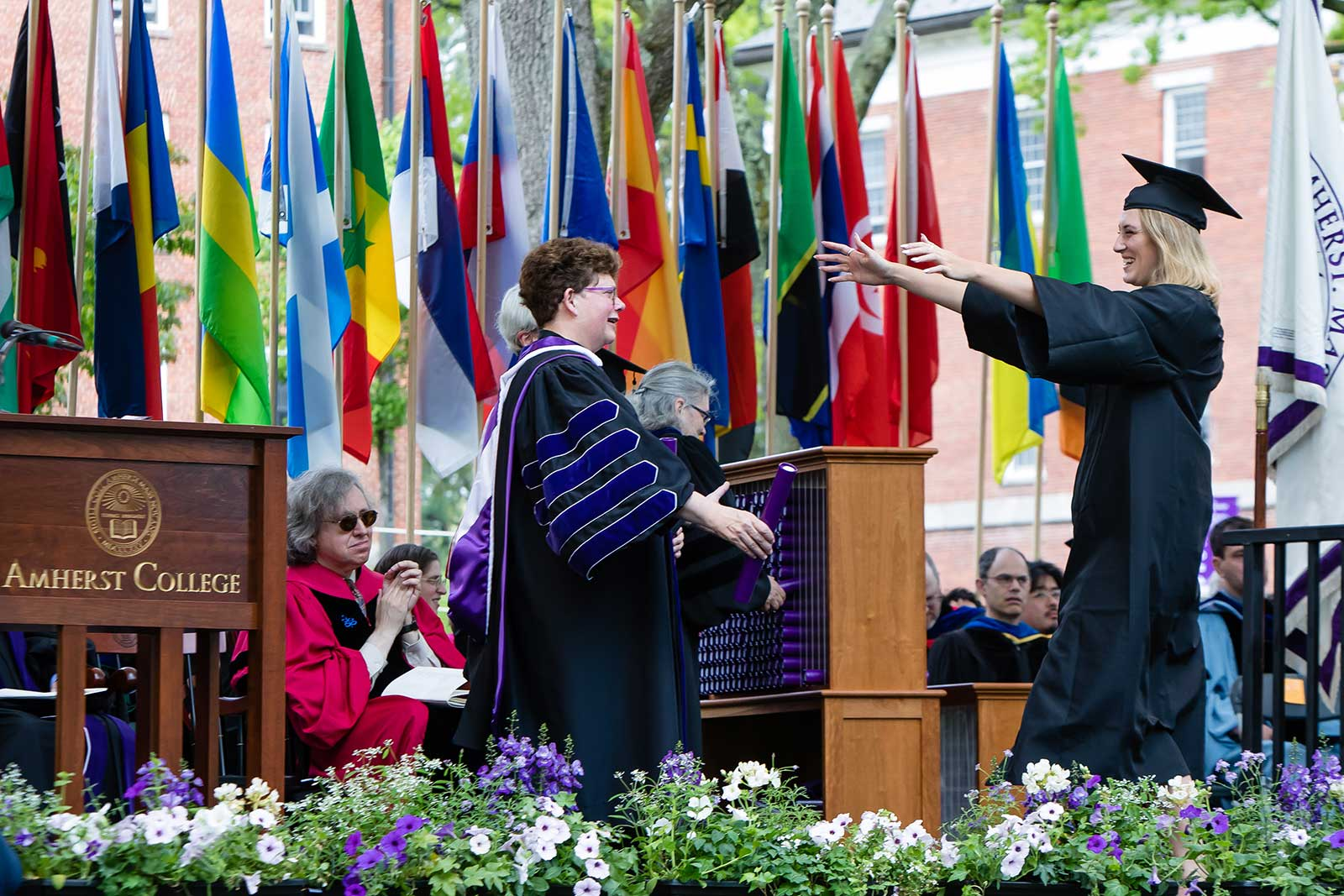 President Martin embracing a new graduate