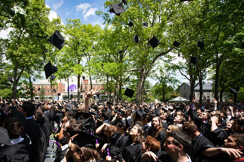Students toss their graduation caps at the end of the ceremony