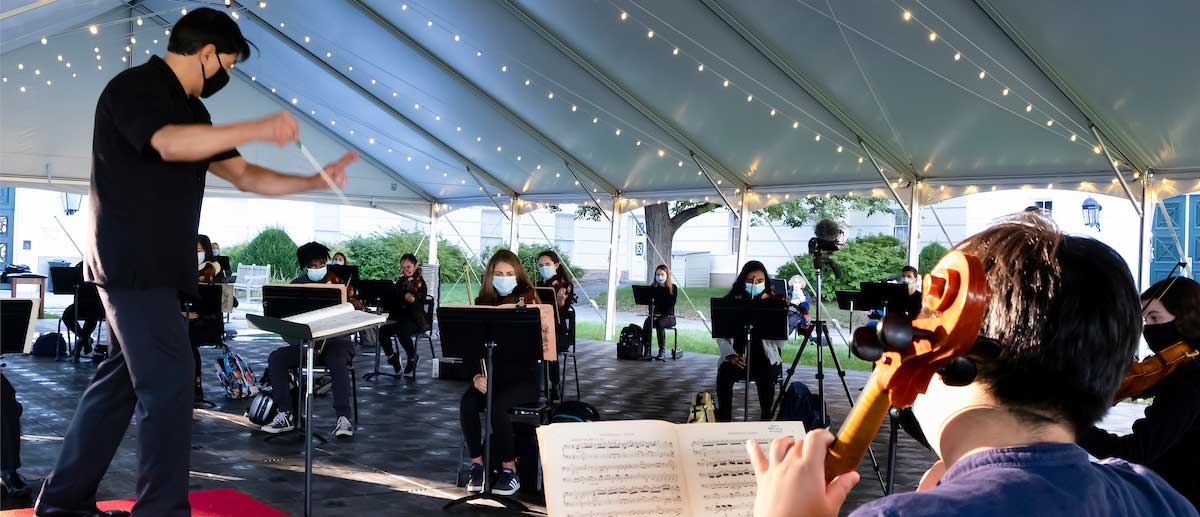 symphony orchestra students rehearse outside under a tent