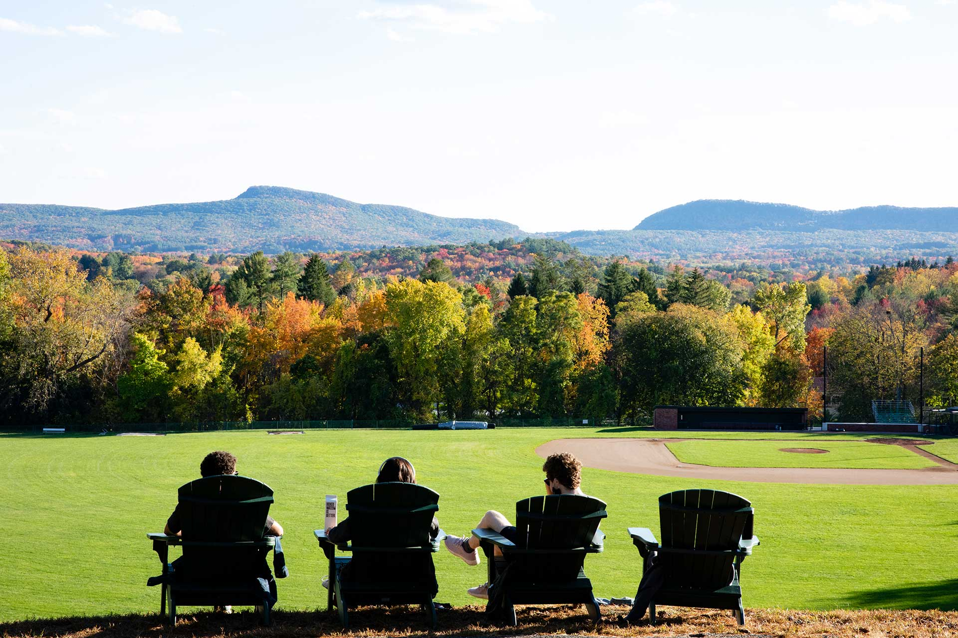 Three students in adirondack chairs facing the mt holyoke range