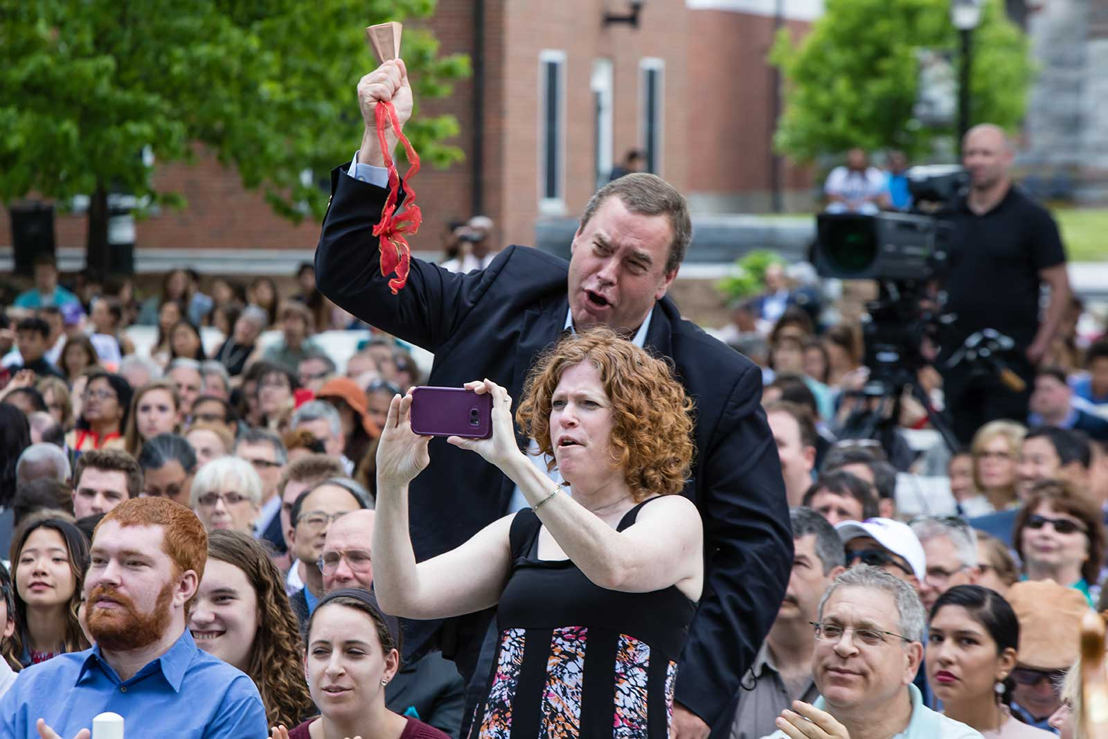 Family members taking photos during Commencement