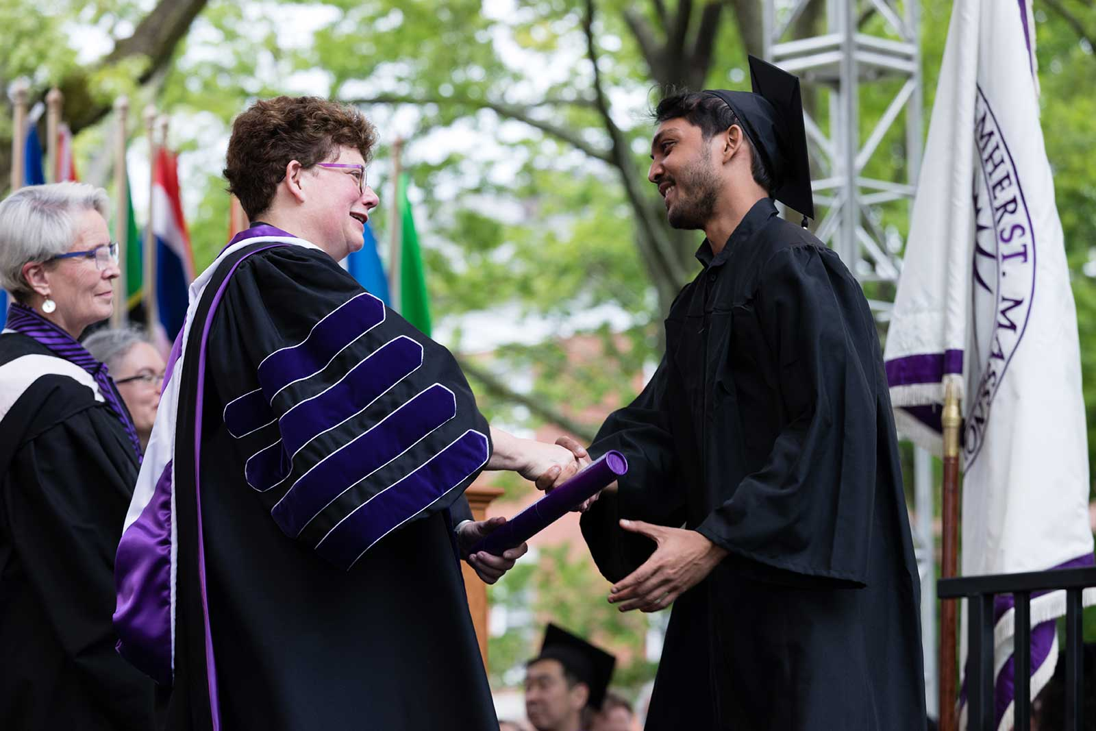 President Martin shaking hands with a graduate