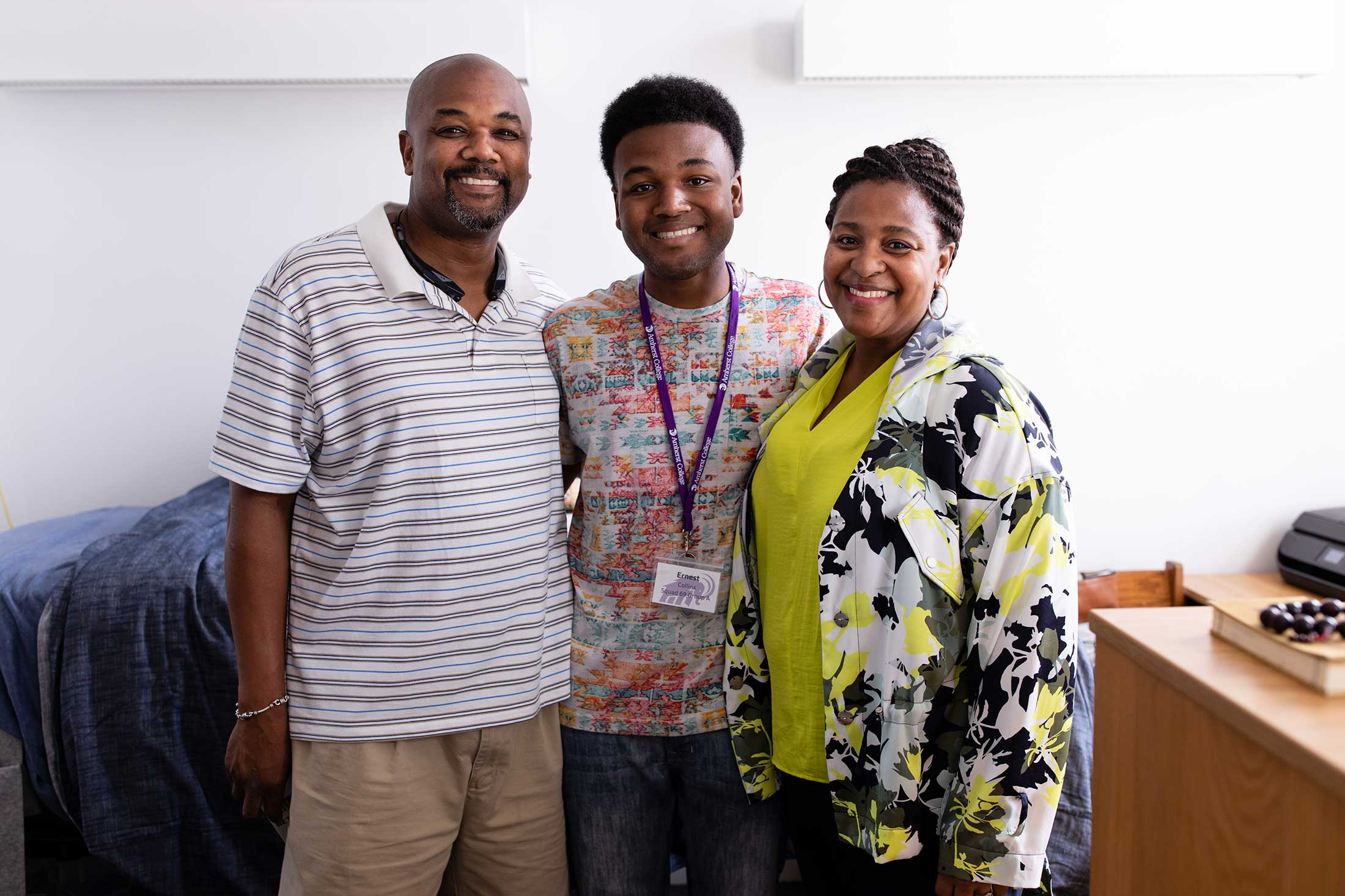 A first year student poses between his mother and father inside his new residence hall.